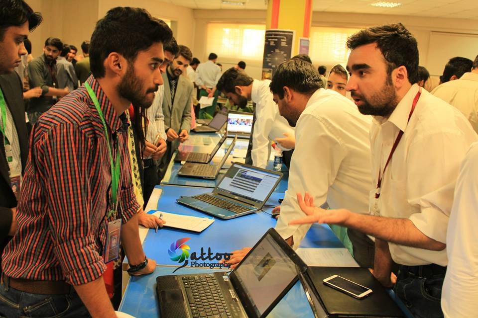 A student giving demo of his project to a visitor. Photo by Gattoo Photography